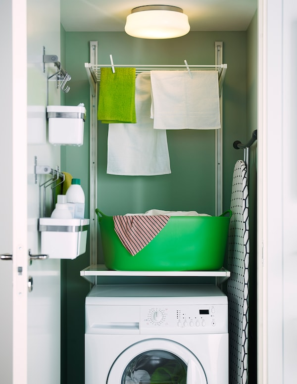 Tendedero de IKEA fijado a la pared, encima de una lavadora en un armario.