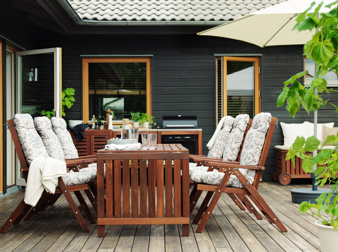 Terassi, jossa kuusi puista nojatuolia pehmusteilla, puinen pöytä ja takana musta grilli.