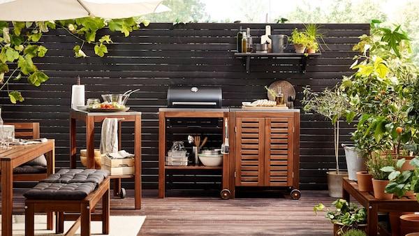 Terassilla on tummanruskeat ÄPPLARÖ-sarjan massiivipuusta valmistetut kalusteet, grilli ja ympärillä kasveja