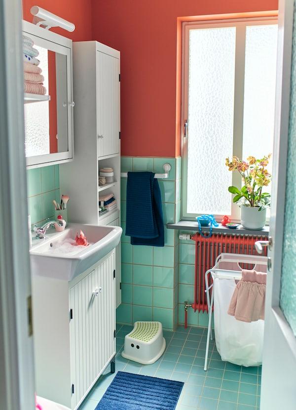 Teremts helyet a fürdőszobában az IKEA SILVERÅN fehér magasszekrényekkel, ajtókkal és hellyel a mosókonyha számára a JÄLL összecsukható fehér szennyestartóval és állvánnyal.