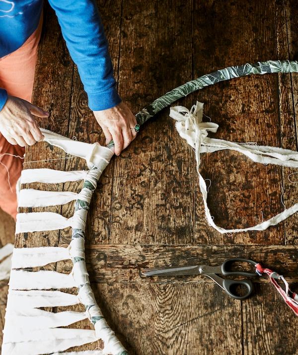 Természetes színű anyagokat kötnek kézzel egy hulahopp karikára.