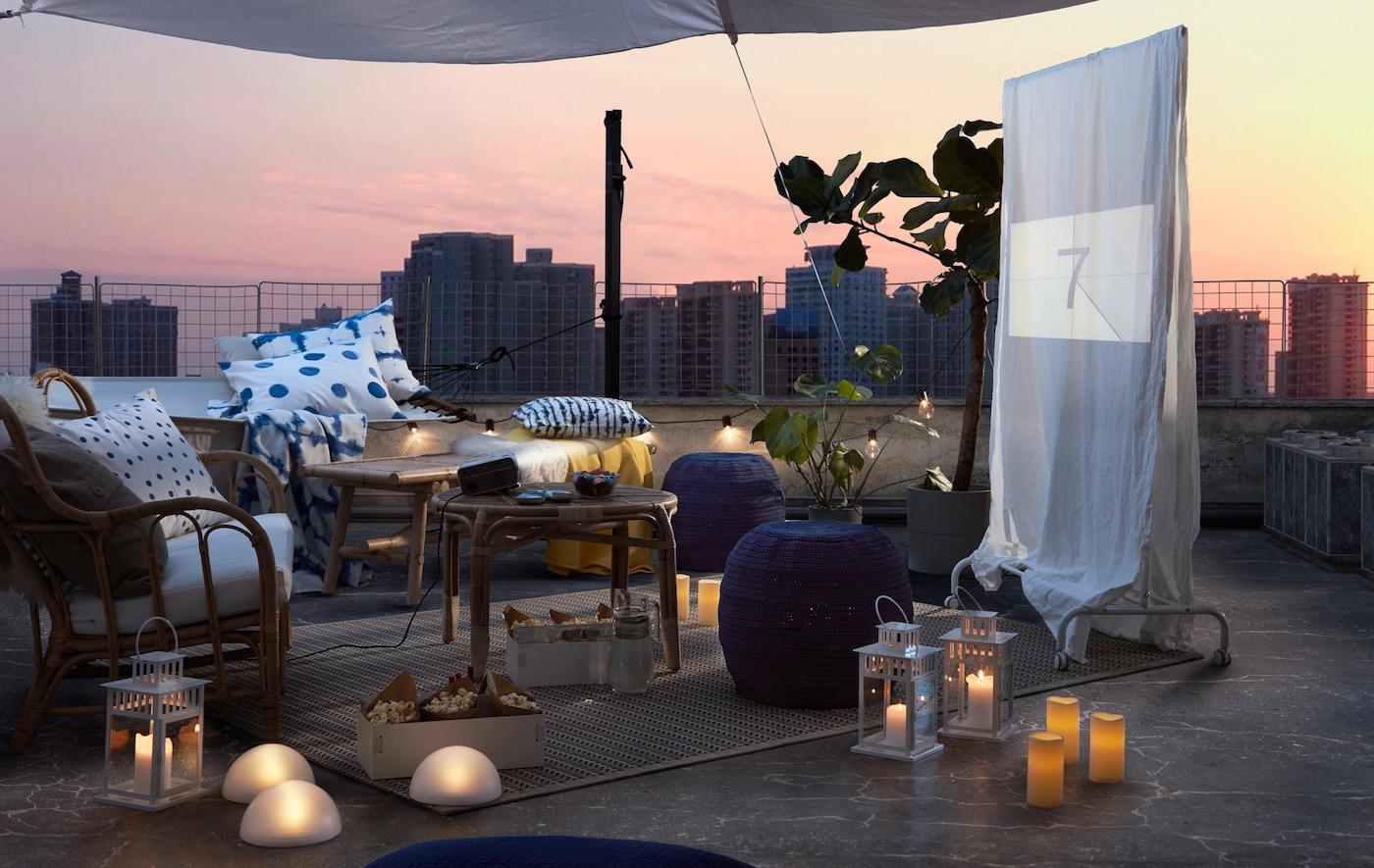 Terraço, disposição de assentos ao ar livre, iluminação LED e têxteis ao anoitecer. Um ecrã improvisado com um filme prestes a começar.