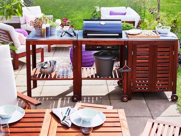 Terrasse avec barbecue au charbon de bois ÄPPLARÖ/KLASEN avec desserte et armoire en acacia, derrière une table d'extérieur.