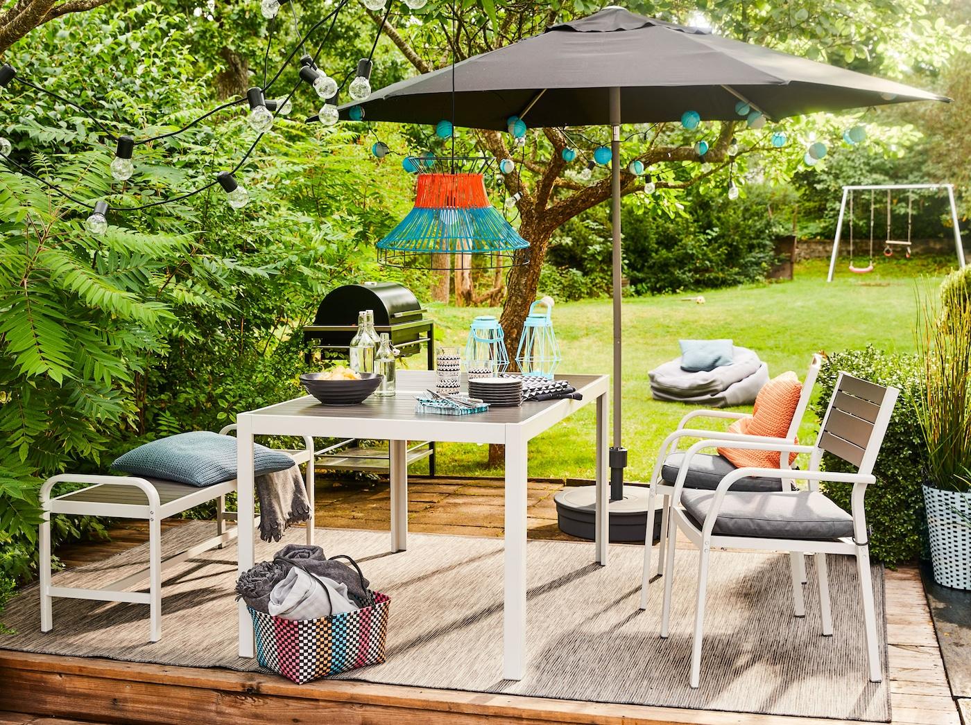 Terrasse im grünen Garten mit SJÄLLAND Tisch, 2 Stühlen, Sonnenschirm & Kissen von IKEA.