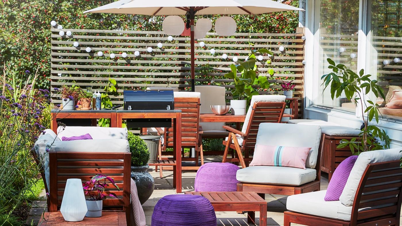 Terraza con grellada, conxunto de sofás de catro asentos en madeira, parasol beixe, pufs morados e coxíns de exterior de cor beixe.