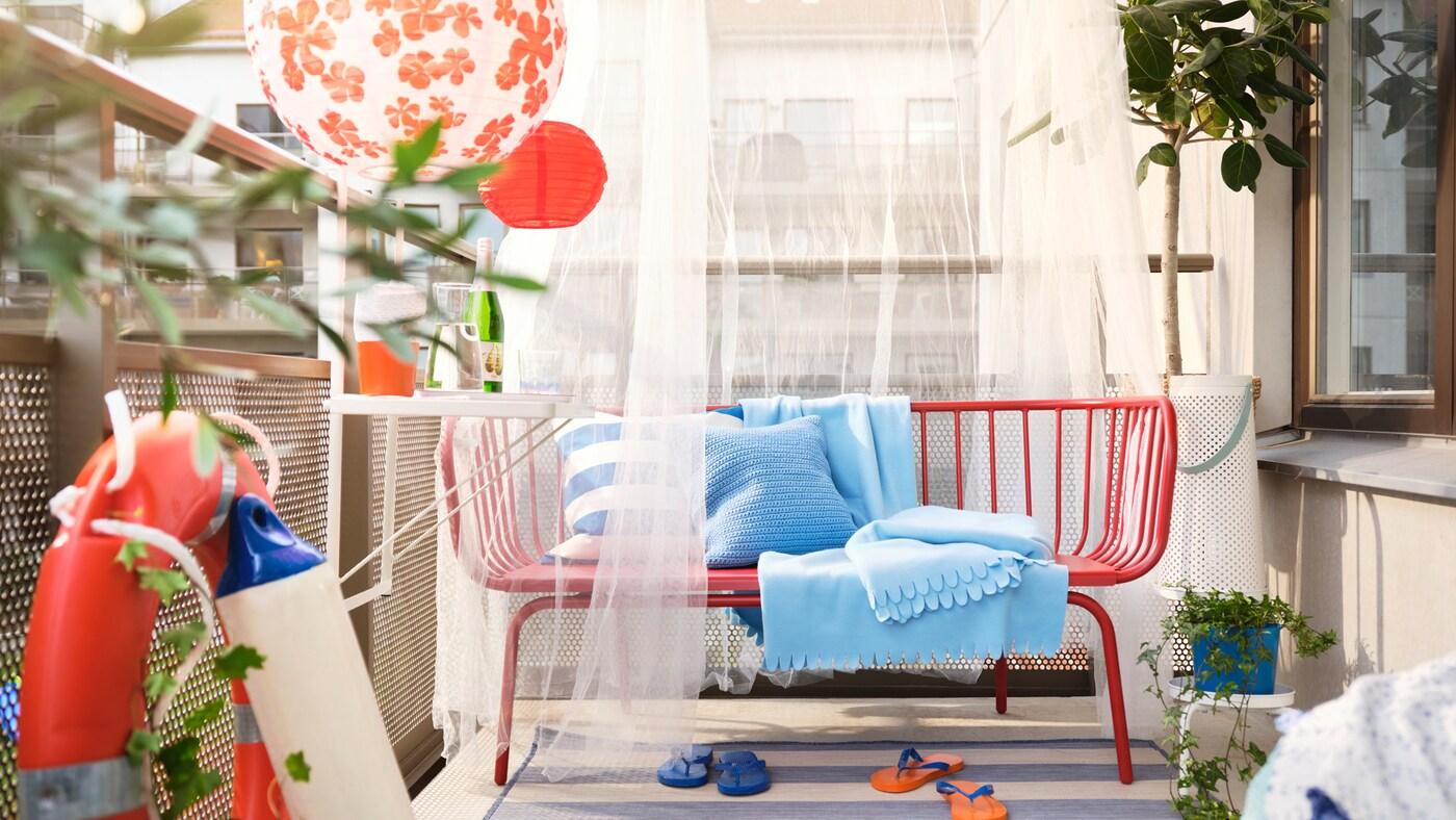 Terraza cun sofá de exterior BRUSEN vermello con coxíns e mantas azuis, unha mesa de terraza TORPARÖ e lámpadas LED solares.