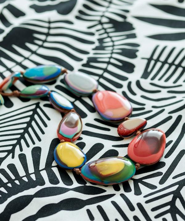 Țesătură cu model în alb și negru pe care este așezat un colier din mărgele sferice în diferite culori.