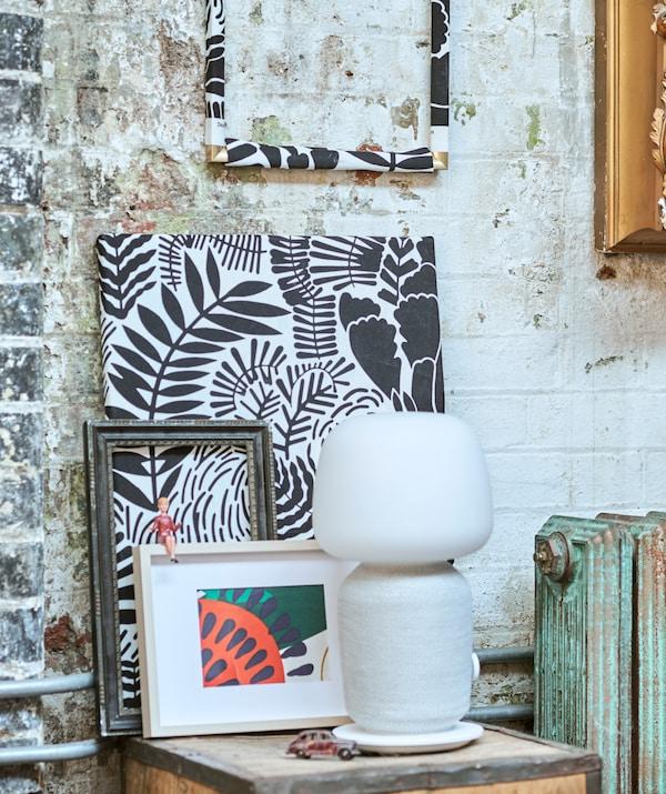Tessuti fantasia incorniciati in modi diversi appoggiati a una parete di mattoni e una lampada bianca con cassa incorporata su una cassa di tè - IKEA