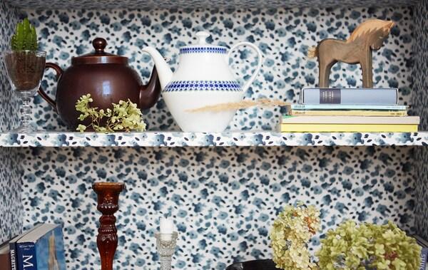 Teteras, libros y adornos varios en las baldas, cubiertas de tela con detalles de flores azules.
