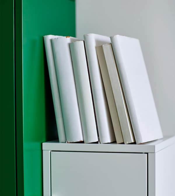 Textbooks bound in white paper sit on top of a white desk organizer.