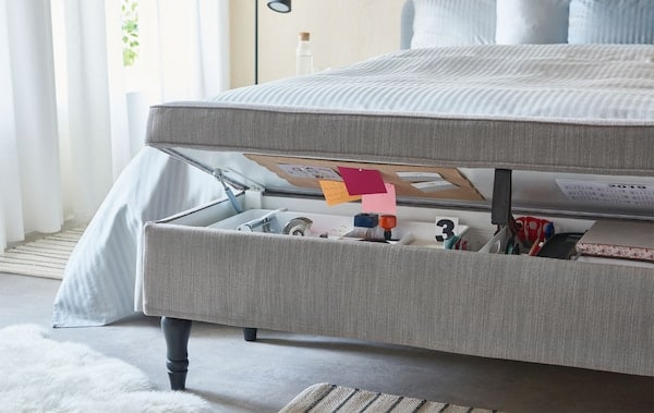 Textile-covered, combined bench and storage unit ajar at the foot end of a bed holding the contents of a typical home office.