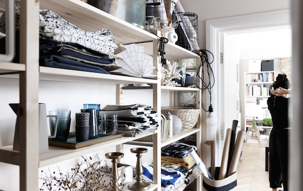 Textiles and tableware displayed on open storage.