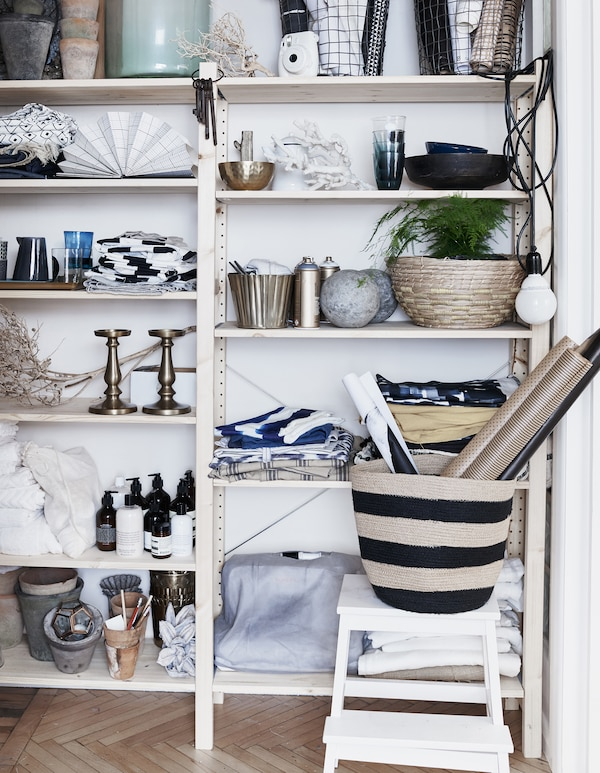 Textiles, plants and ornaments on a shelving unit.