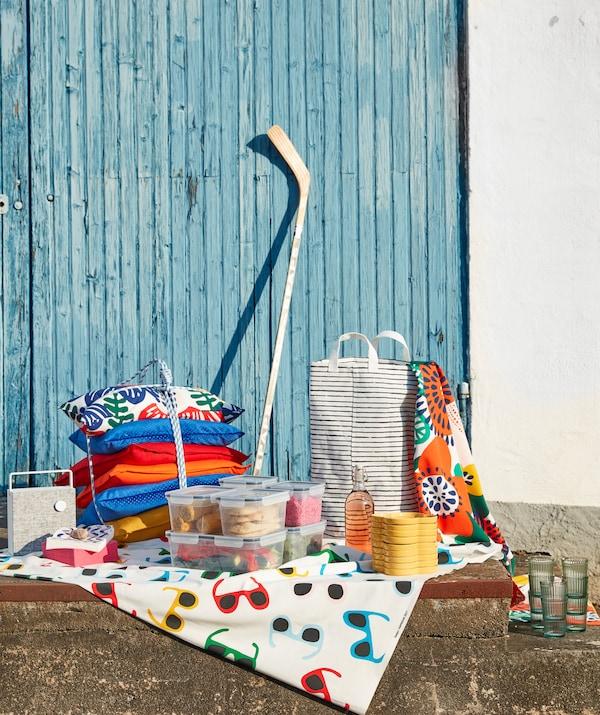 Textilien, Teller, Fingerfood und ein KLUNKA Wäschesack in Weiß/Schwarz, um alles darin zur Sommerparty zu transportieren.
