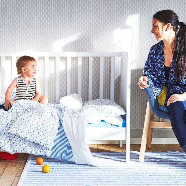 طفل جالس في سرير أطفال SUNDVIK مغطى بمفارش سرير باللونين الأزرق والأبيض وينظر إلى والدته عند طرف السرير.