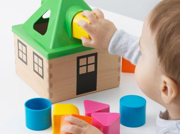 طفل صغير يلعب بلعبة من ايكيا مصنوعة من الخشب وقطع بلاستيكية ملونة خالية من البيسفينول A.