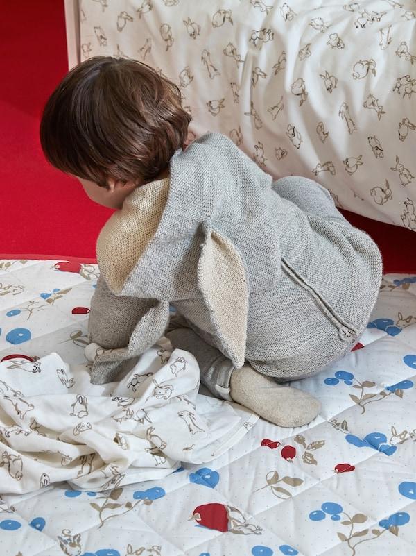 طفل صغير يرتدي أوفرول شكل أرنب يزحف على بطانيةمبطنة RÖDHAKE، بجانب سرير أطفال مرتب بمفارش سرير RÖDHAKE.