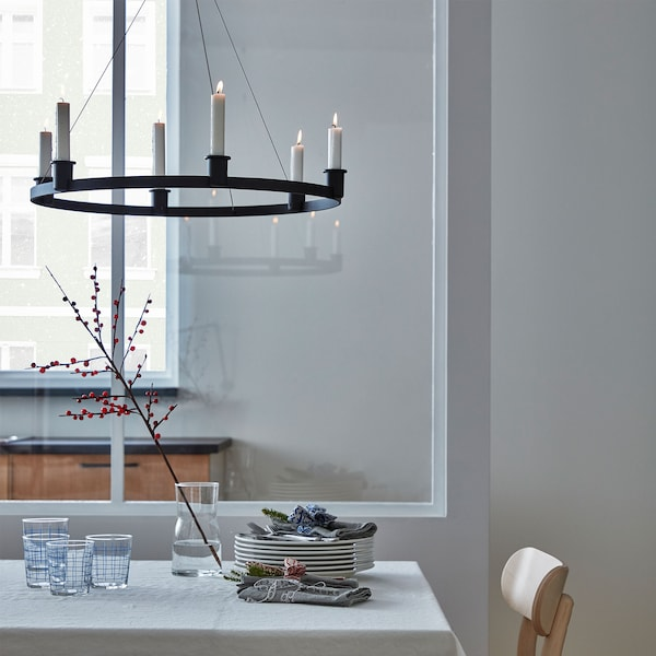 The aluminium VÄRMER chandelier with lit candles hangs over a minimalist dining table with plates and glasses.