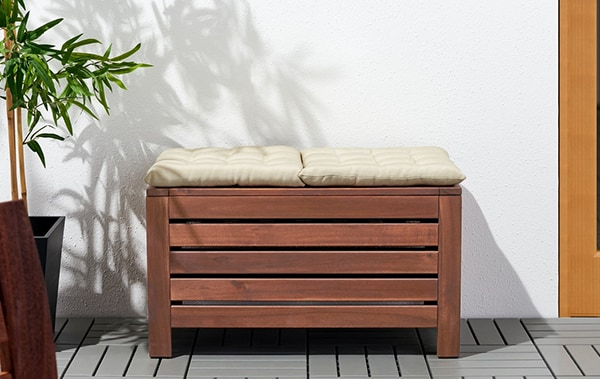 The APPLARO storage bench being used as a table with an outdoor sofa and plant stand with greenery on a balcony.