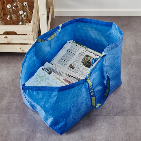 The blue FRAKTA bag sitting on the ground with newspapers inside.