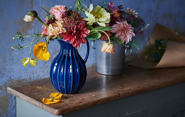 The blue VANLIGEN vase on the wood top and the multicolored flowers in the vase, and the sky blue wall with the paint peeled off.