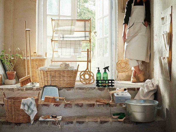 The BORSTAD collection of products sit in a sun-filled doorway, while a woman holding the carpet beater stands beside them.