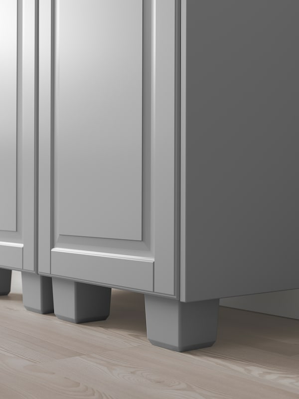 The bottom corner of a grey kitchen cabinet with matching grey legs.