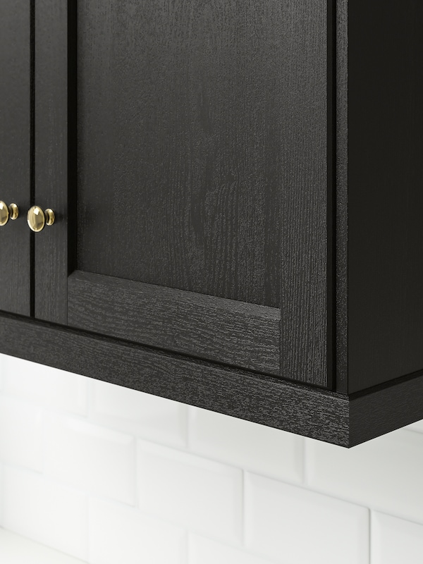 The bottom corner of a kitchen cabinet with LERHYTTAN doors in stained black.