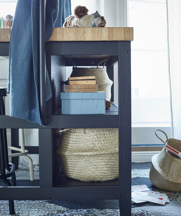 The built-in shelves of VADHOLMA kitchen island holding baskets and boxes.