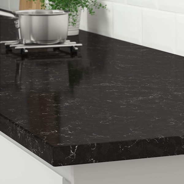The corner of a black marble effect countertop on a white kitchen cabinet with a stainless steel pot on a trivet.