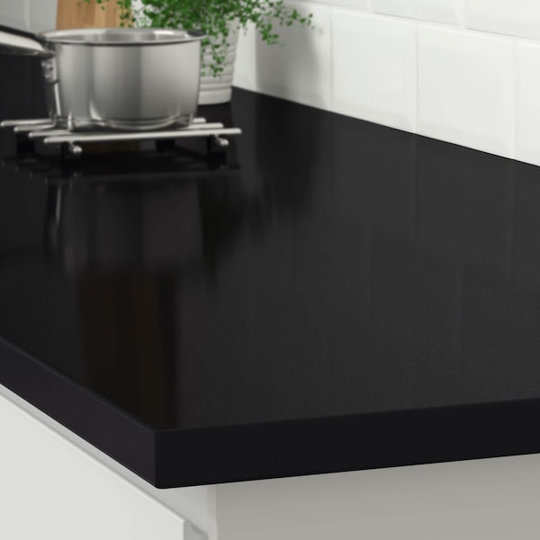 The corner of a black stone effect countertop on a white kitchen cabinet with a stainless steel pot on a trivet.