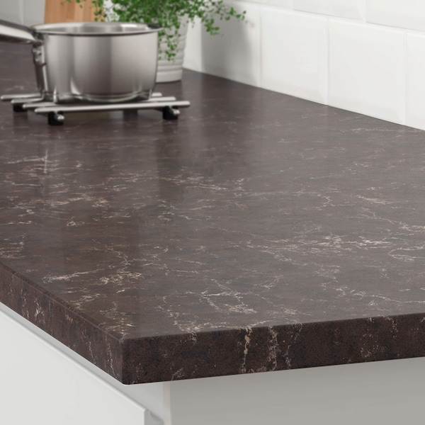 The corner of a dark brown marble effect countertop on a white kitchen cabinet with a stainless steel pot on a trivet.