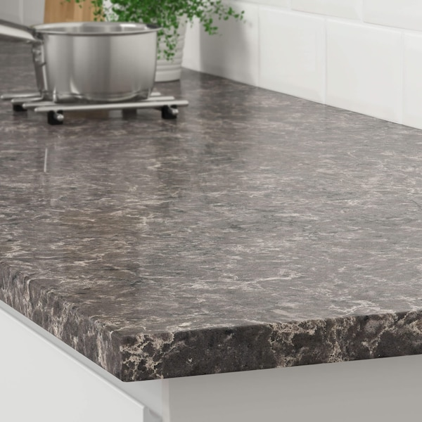 The corner of a gray marble effect countertop on a white kitchen cabinet with a stainless steel pot on a trivet.