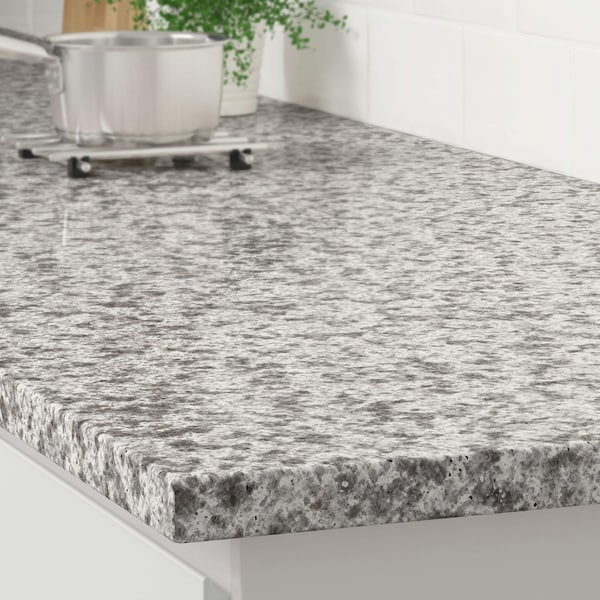 The corner of a gray mineral effect countertop on a white kitchen cabinet with a stainless steel pot on a trivet.