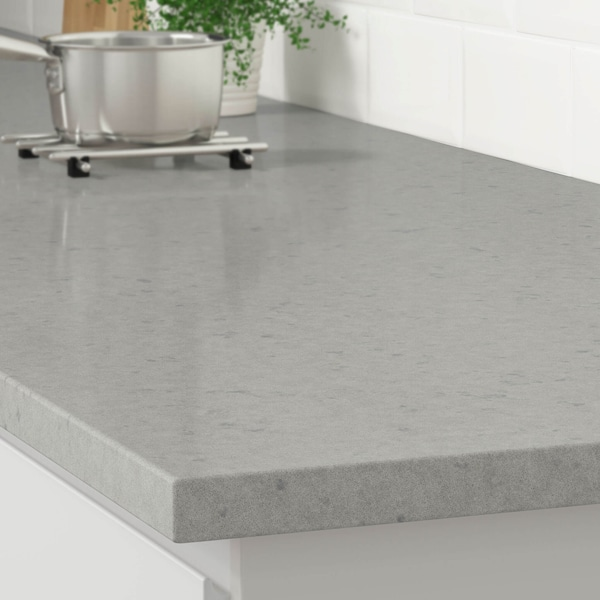 The corner of a gray stone effect countertop on a white kitchen cabinet with a stainless steel pot on a trivet.