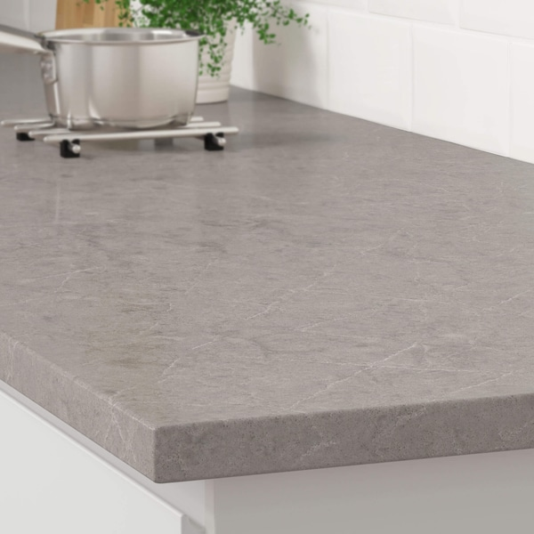 The corner of a gray stone marble effect countertop on a white kitchen cabinet with a stainless steel pot on a trivet.