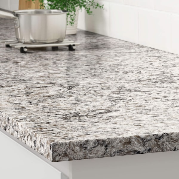 The corner of a light gray beige glitter marble effect counter on a white cabinet with a stainless steel pot on a trivet.