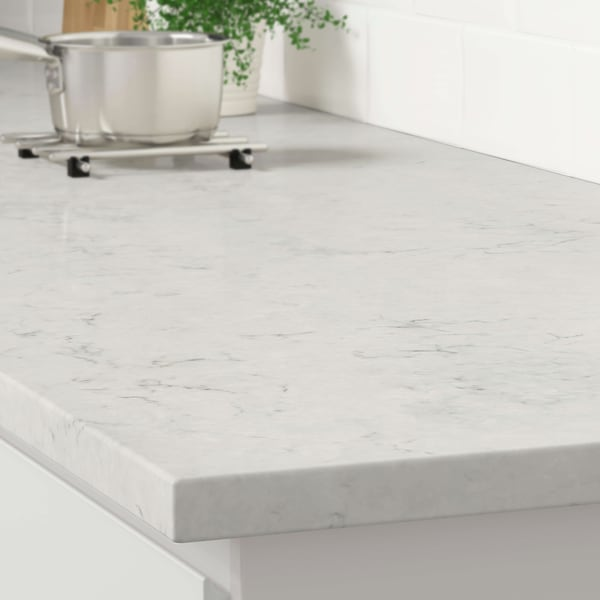 The corner of a light gray marble effect countertop on a white kitchen cabinet with a stainless steel pot on a trivet.