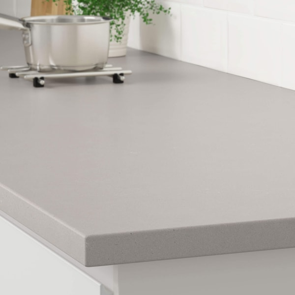 The corner of a light gray stone effect countertop on a white kitchen cabinet with a stainless steel pot on a trivet.