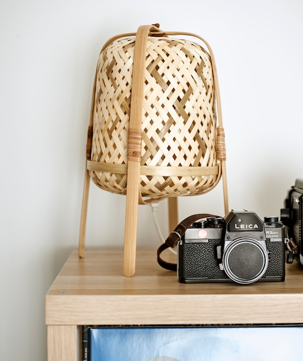 The corner of a light wood shelving unit on top is a vintage camera and a woven wicker table lamp.