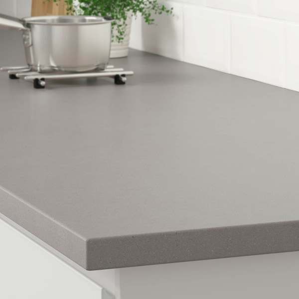 The corner of a matte light gray concrete effect countertop on a white cabinet with a stainless steel pot on a trivet.