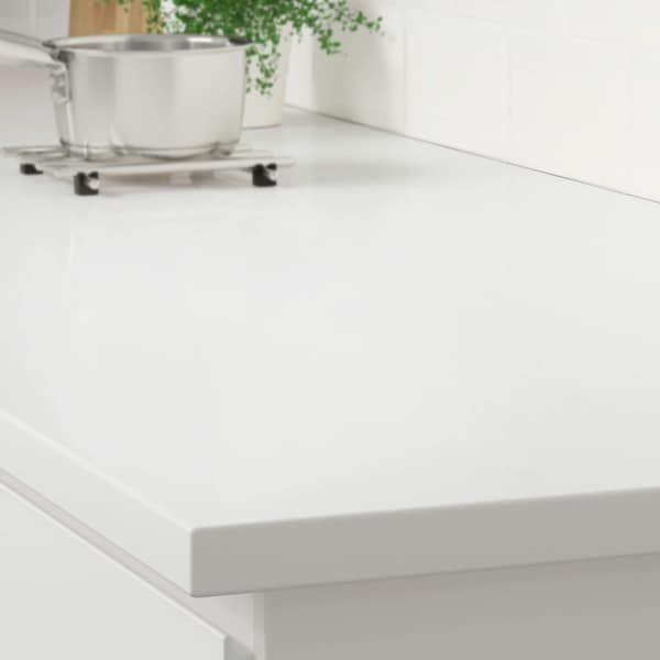 The corner of a white countertop on a white kitchen cabinet with a stainless steel pot on a trivet.