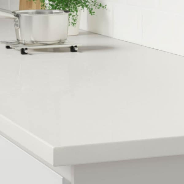 The corner of a white marble effect countertop on a white kitchen cabinet with a stainless steel pot on a trivet.
