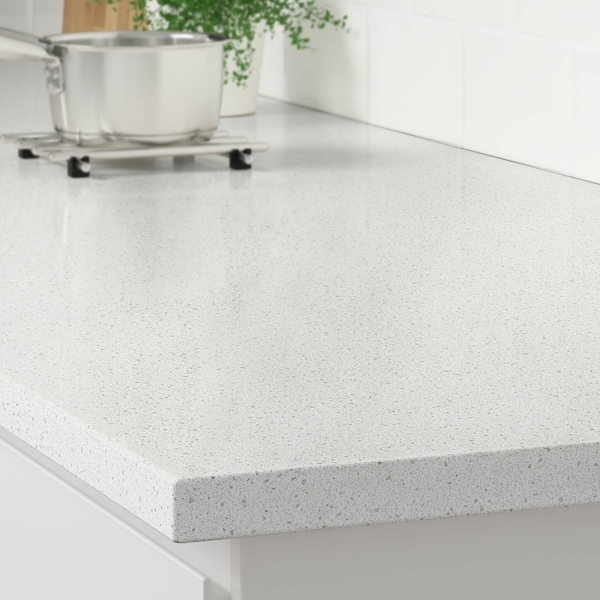 The corner of a white mineral effect countertop on a white kitchen cabinet with a stainless steel pot on a trivet.