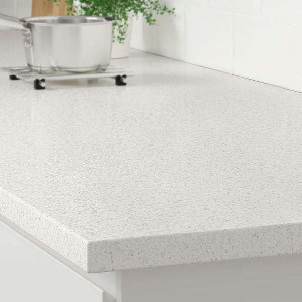 The corner of a white mineral glitter effect countertop on a white kitchen cabinet with a stainless steel pot on a trivet.
