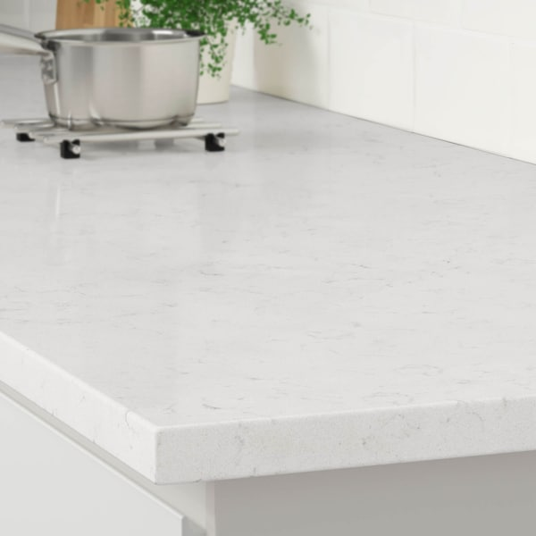 The corner of a white stone marble effect countertop on a white kitchen cabinet with a stainless steel pot on a trivet.