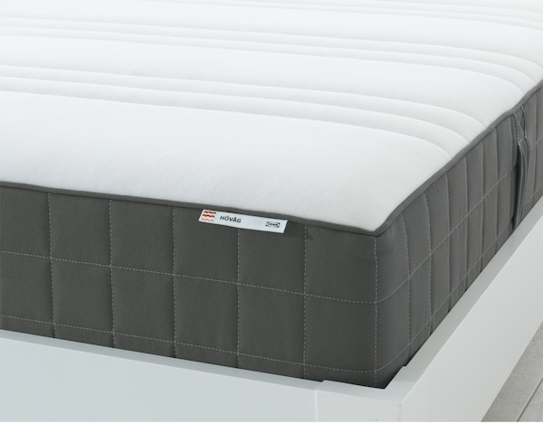 The corner of an IKEA HÖVÅG pocket sprung mattress that is white on the top and dark grey on the sides.