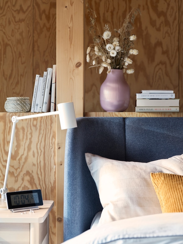 The curved corner of a blue TUFJORD bed, in front of a wooden wall with built-in bookshelf and next to a bedside table.