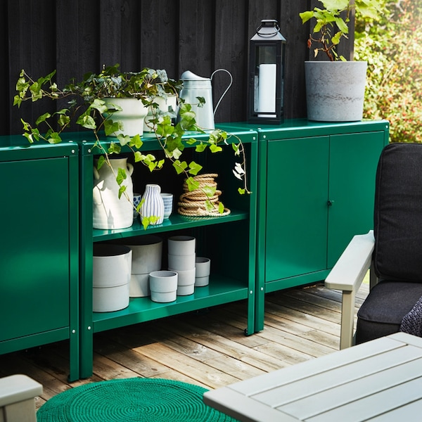 The dark green KOLBJORN storage cabinet filled with outdoor accessories and plants in an outdoor setting.