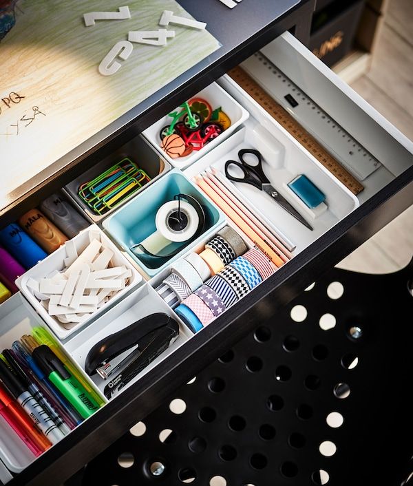 The desk drawer is open to reveal lots of organizers and school supplies.